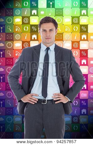 Serious businessman with hands on hips against app wall