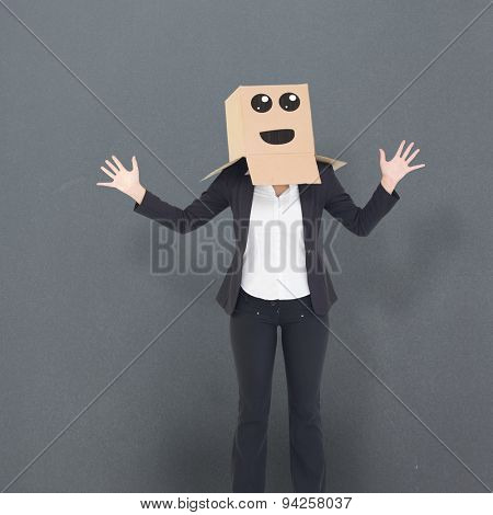 Businesswoman with box over head against grey background