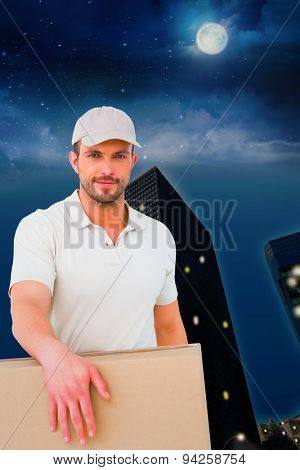 Delivery man carrying package against city at night