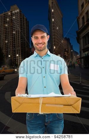 Handsome courier man with parcel against city at night