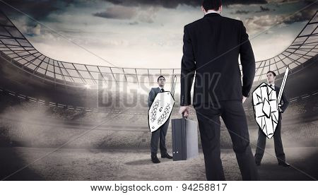 Rear view of businessman holding a briefcase against stadium