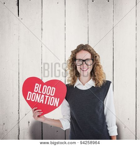 Geeky hipster holding heart card against white wood