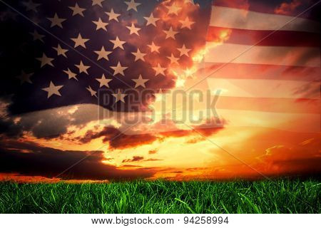 United states of america flag against green grass under dark blue and orange sky