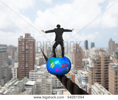 Businessman Standing On Top Of Ball Balancing On Wire