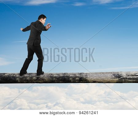 Businessman Walking On The Tree Trunk