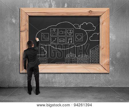 Businessman Drawing App Icons On Blackboard