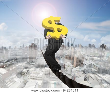 Businessman Carrying Gold Dollar Sign Balancing On Wire