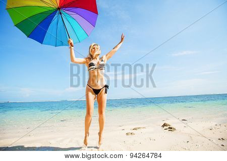 Young skinny girl in blue shorts with colourful rainbow umbrella jumps on the beach