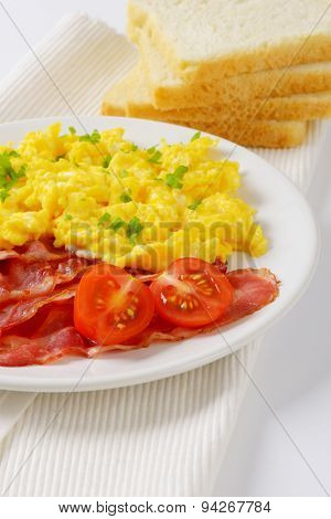 plate of scrambled eggs and fried bacon and slices of bread on white place mat