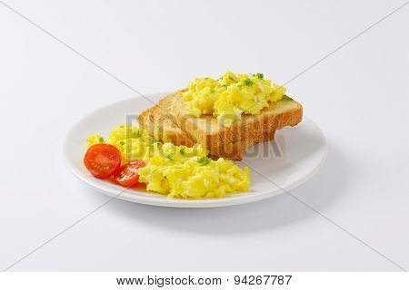 plate of scrambled eggs and slices of bread on white background