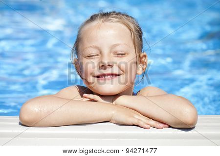 Happy little Girl in blue bikini swimming pool