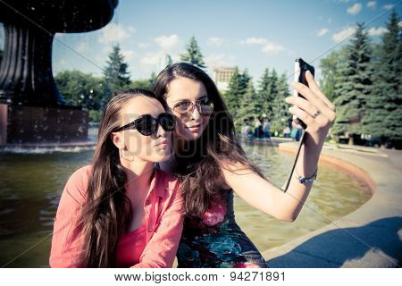 Two Young Women Taking A Selfie Outdoors