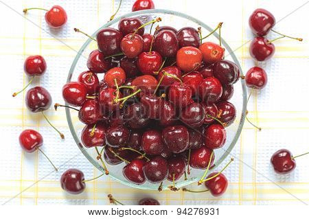 Red sweet cherries with water drops in the glass bowl
