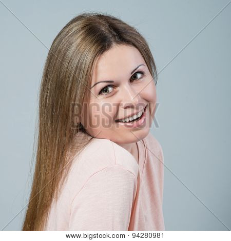 Young Woman Smiling On Grey Background