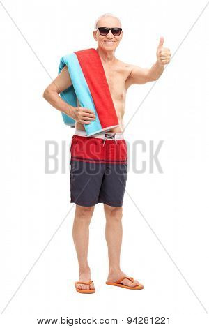 Full length portrait of a senior in blue swim trunks carrying a towel over his shoulder and giving a thumb up isolated on white background