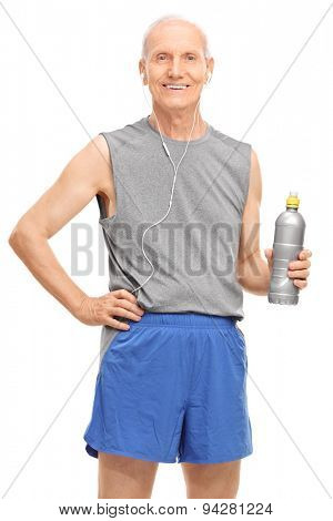 Vertical shot of a senior man in sportswear listening music on headphones and holding a water bottle isolated on white background