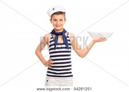 Cheerful little kid in a sailor outfit holding a paper boat and looking at the camera isolated on white background