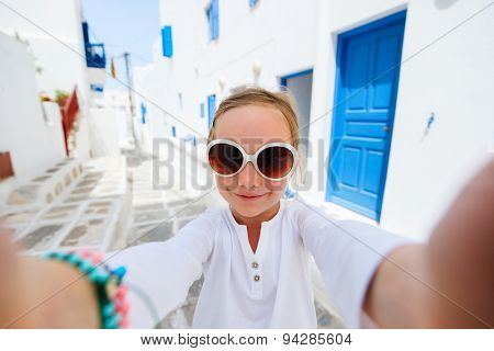 Little tourist girl taking selfie with mobile phone on a street of traditional greek village on Mykonos island