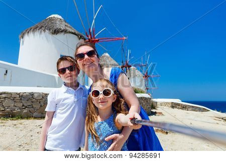 Family of mother and kids taking selfie with a stick in front of windmills at popular tourist area on Mykonos island, Greece
