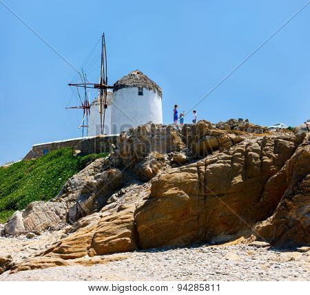 Family of mother and kids in front of windmills at popular tourist area on Mykonos island, Greece