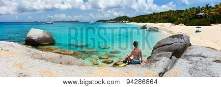 Young woman with snorkeling equipment enjoying view of a tropical beach sitting on granite boulder at Virgin Gorda, British Virgin Islands, Caribbean