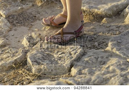 Feet With Sandals On The Rock.