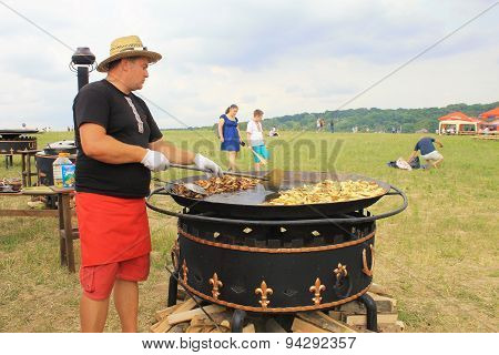 Man Cooking Crisp Potato On The Huge Grill Outdoor Pan, Pirogovo, Kiev, Ukraine