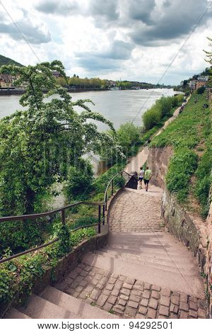 HEIDELBERG, GERMANY - APRIL 26: Couple Walking Along Riverfront Trail Bordered by Green Foliage on Bank of Neckar River, Heidelberg, Baden-Wurttemberg, Germany on April 26, 2015