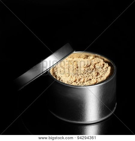 Jar with loose cosmetic powder isolated on black