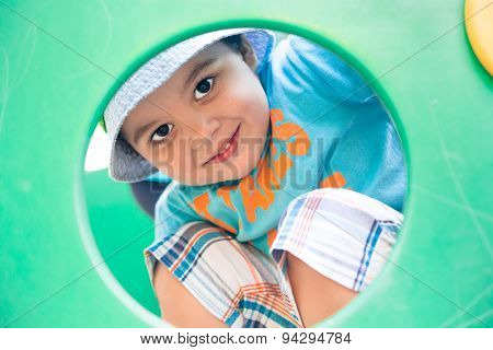 boy looking through a round hole