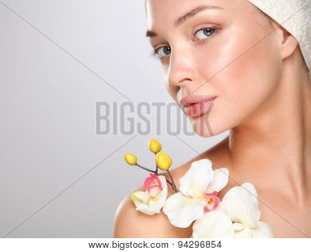 Woman in towel with orchid flowers .