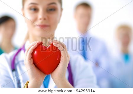 Female doctor with stethoscope holding heart .