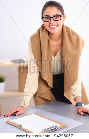 Attractive businesswoman standing  near desk in office