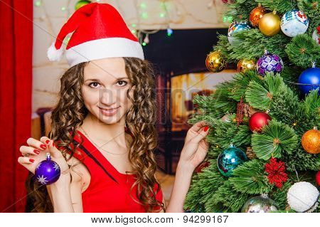 Young Girl Hangs On A Christmas Tree Ball