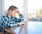 stock photo of sad boy  - Bemused and sad 12 years old children boy sitting at the wooden desk - JPG
