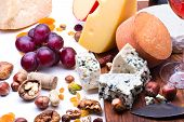 picture of dry fruit  - Cheeses with dried fruits and nuts on wooden board - JPG