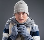 stock photo of freezing  - Freezing man in winter clothes drinking hot tea - JPG