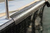 stock photo of reinforcing  - Black Carbon fibre reinforcement on black shining Sailboat with reflection and water drops  on the surface - JPG