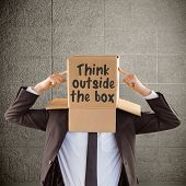 stock photo of anonymous  - Anonymous businessman pointing to box against grey room - JPG
