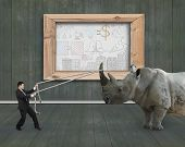 image of rope pulling  - Businessman pulling rope against a huge rhinoceros with business concept doodles whiteboard on wooden indoors background - JPG