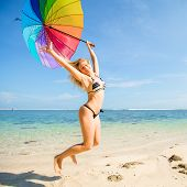 picture of skinny girl  - Young skinny girl in blue shorts with colourful rainbow umbrella jumps on the beach with clear blue sky and ocean on background - JPG