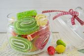 stock photo of jar jelly  - Colorful jelly rolls in a decorated glass jar on a decoupage decorated table - JPG