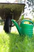 stock photo of wheelbarrow  - Watering placed on the grass by the wheelbarrow in a beautiful garden - JPG