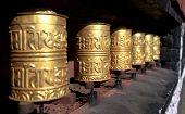 picture of sanskrit  - golden buddhist prayer wheels with buddhist tibetan symbols - JPG