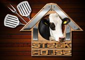 picture of cow head  - Wooden and metallic sign in the shape of house with text Steak House head of cow spatulas and fork - JPG