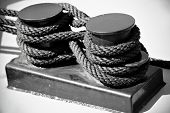 foto of black tie  - Industrial shot wit nautical black rope tied on a ship as figure eight knot  - JPG