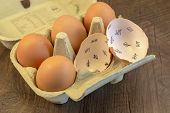 image of count down  - Egg shells shown lying on a wooden background with marks inside counting down the days till hatching - JPG