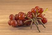 stock photo of creepy crawlies  - Grapes lying on a wooden surface with a spider crawing accross them - JPG