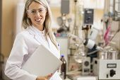 foto of chemistry technician  - Young chemist with laptop computer standing in chemistry lab - JPG