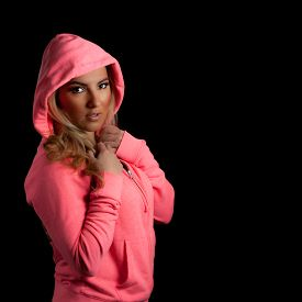 picture of hoodie  - A blonde Latina girl in a pink hoodie isolated on a black background with her hands in pockets - JPG